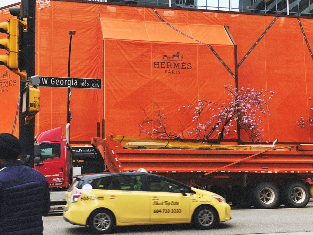 yellow hatchback passing by orange freight truck