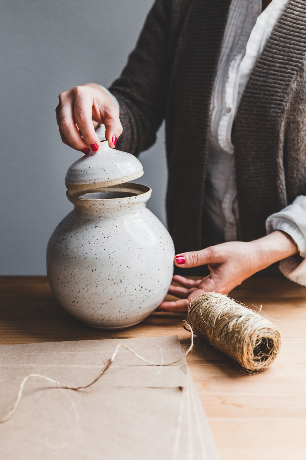 gray ceramic jar with lid and brown thread