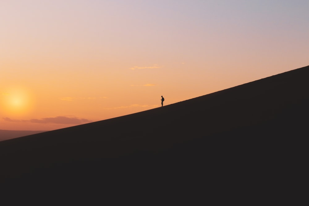silhouette of person standing on crest of hill under orange sky at sunset