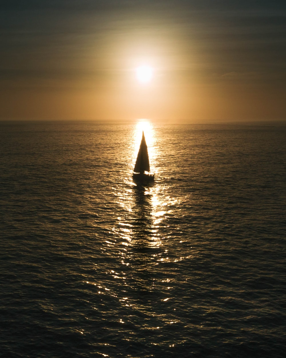 sailboat on calm body of water during golden hour