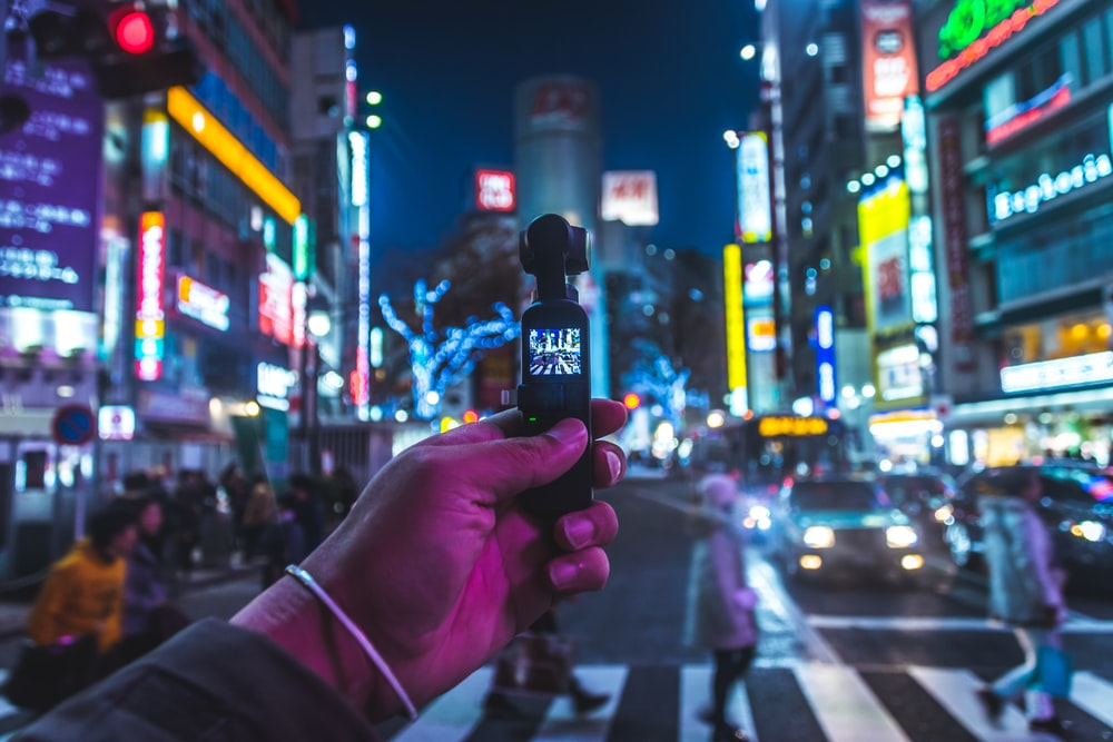 person taking photo of people walking across pedestrian