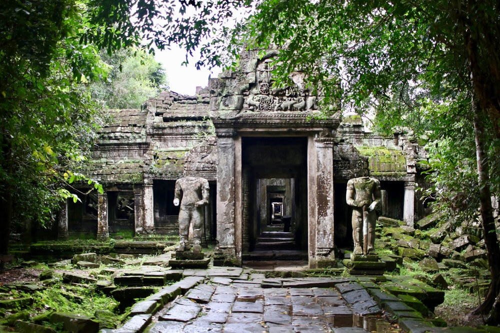 two grey stone statues on both sides of building entrance