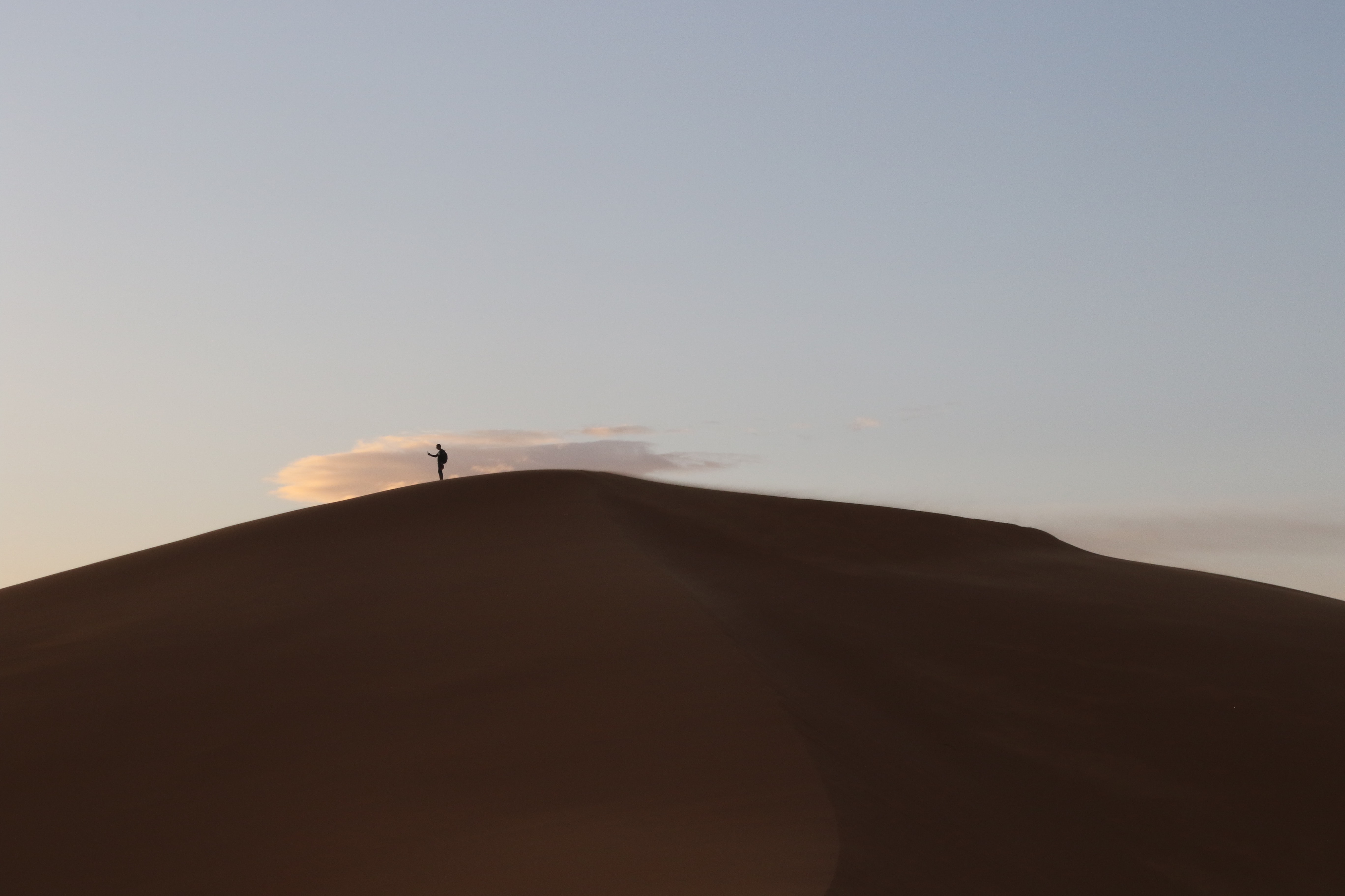 person standing on brown sand mountain