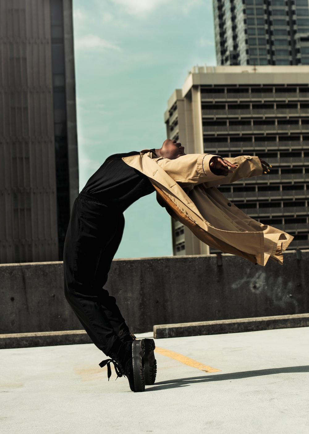 man in brown coat bending back