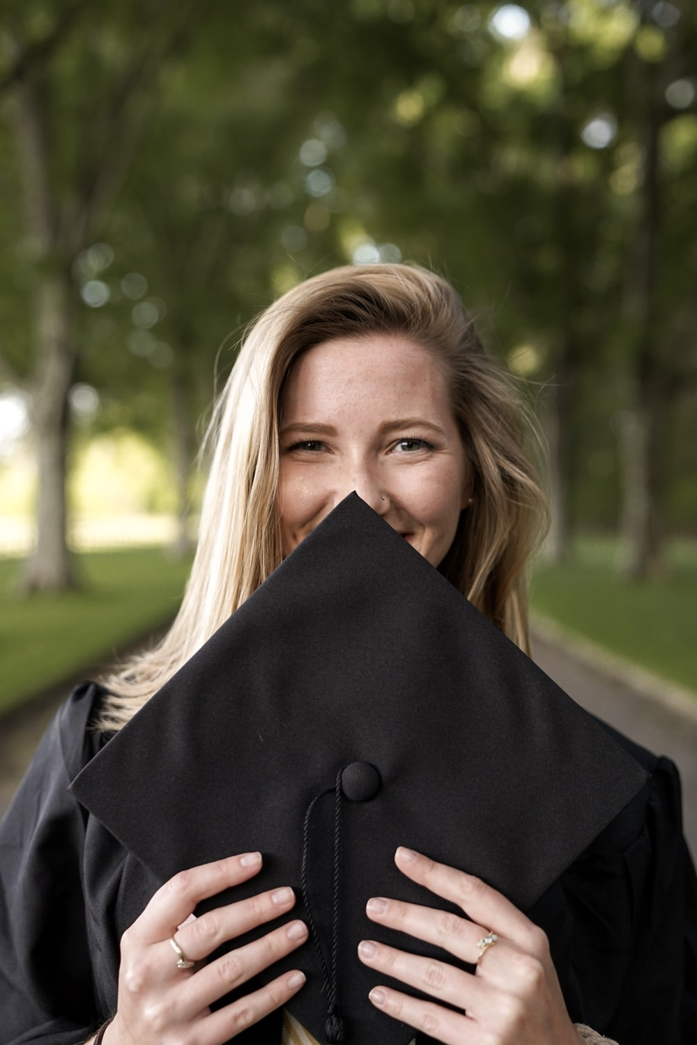 smiling woman slightly covering face with mortar board