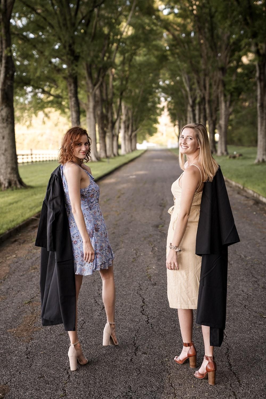two women walking on road near trees