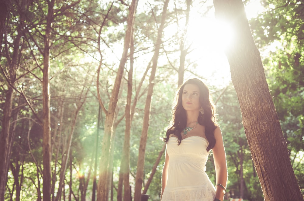 woman wearing white dress standing beside tree