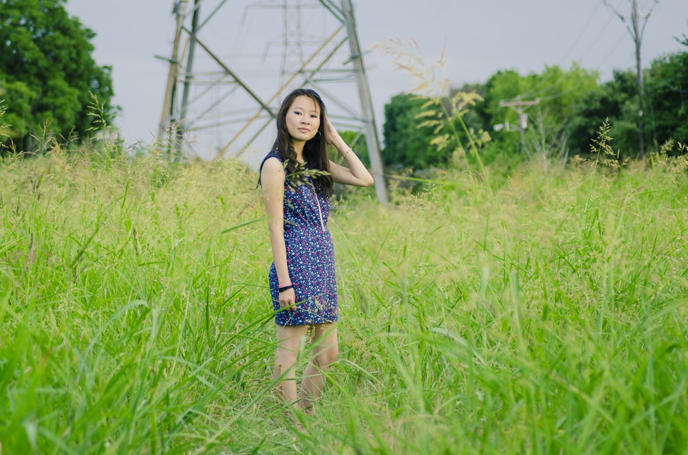 woman standing on grass field near electric post