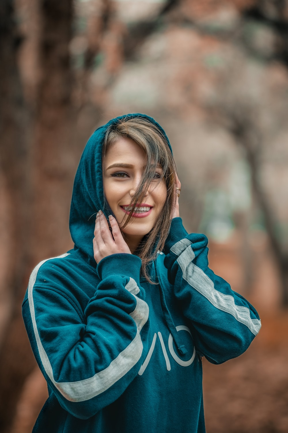smiling woman wearing blue hoodie in selective focus photography