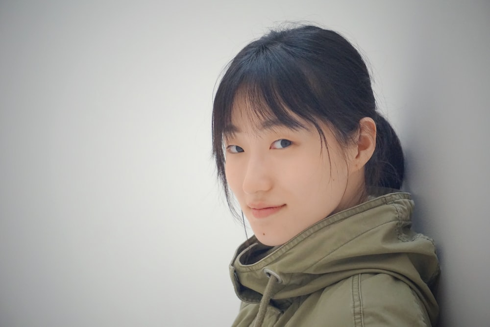 woman wearing jacket leaning on wall