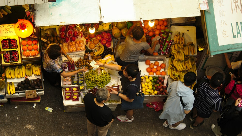 low angle photography of people on market during daytime