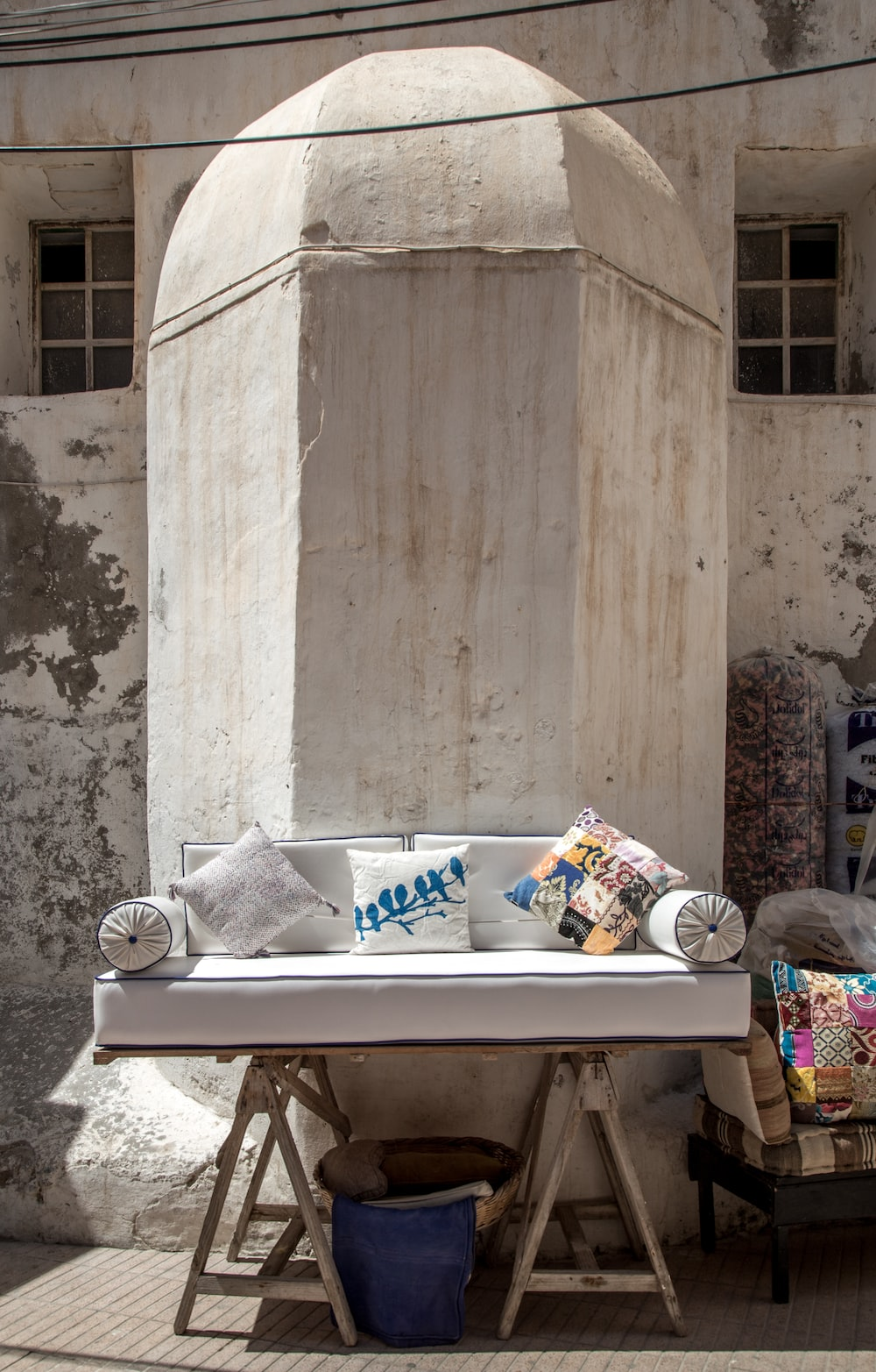 sofa with throw pillows near concrete structure