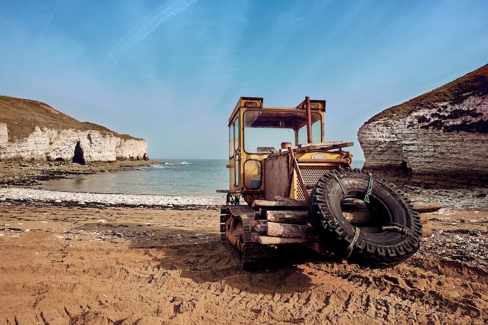 yellow heavy equipment near beach line