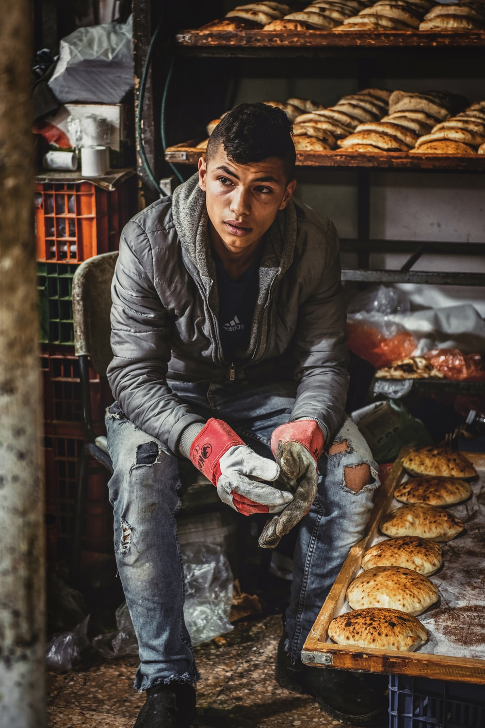 man sitting on chair near baked breads