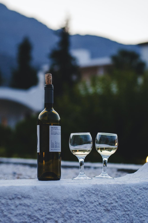 bottle of wine near two glasses of wine