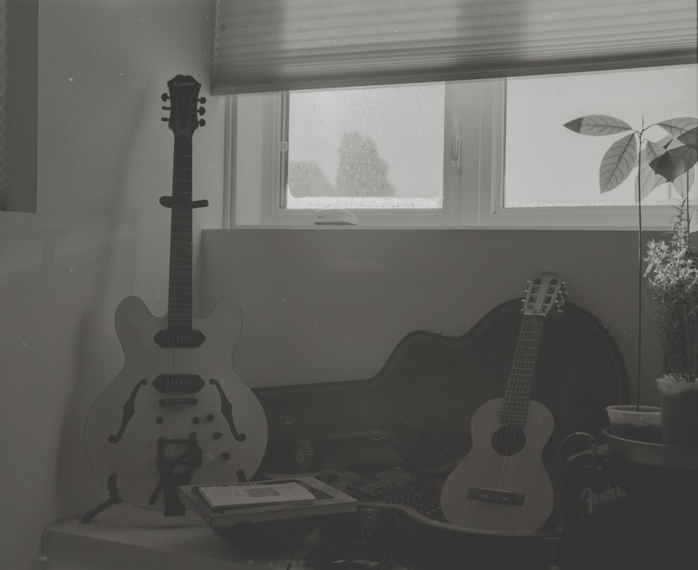two guitars leaning on chairs and table inside room
