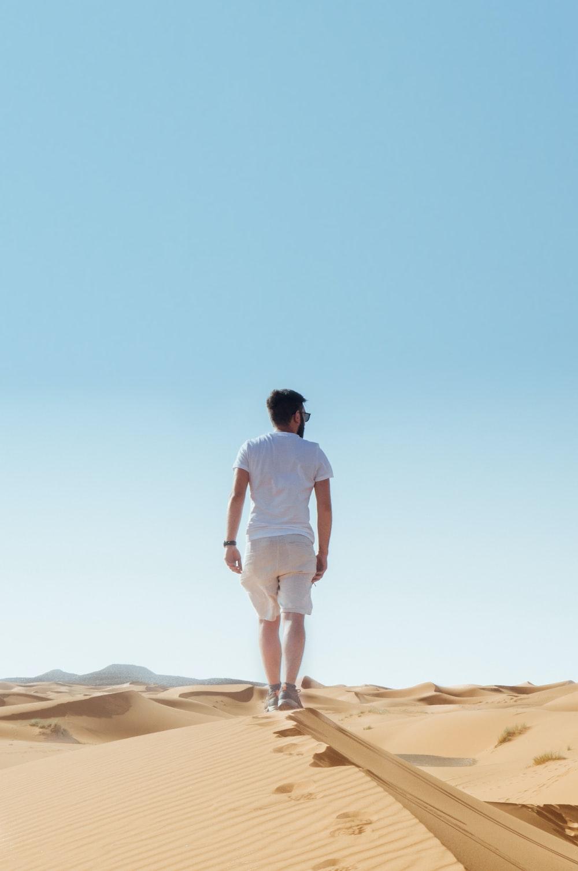 man standing on sand field