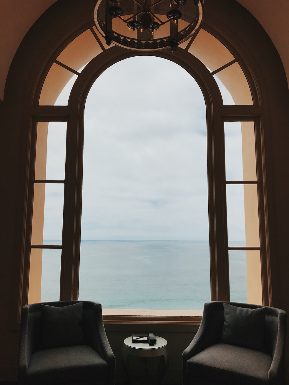 brown wooden framed window and grey padded chairs