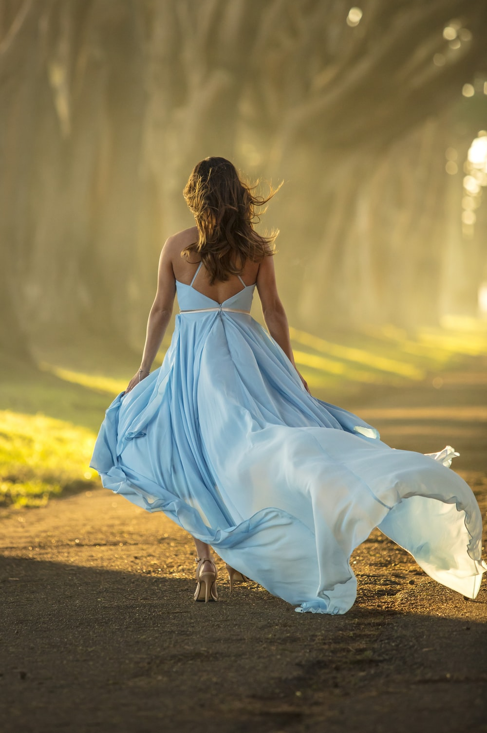 woman in blue dress walking on road during daytime