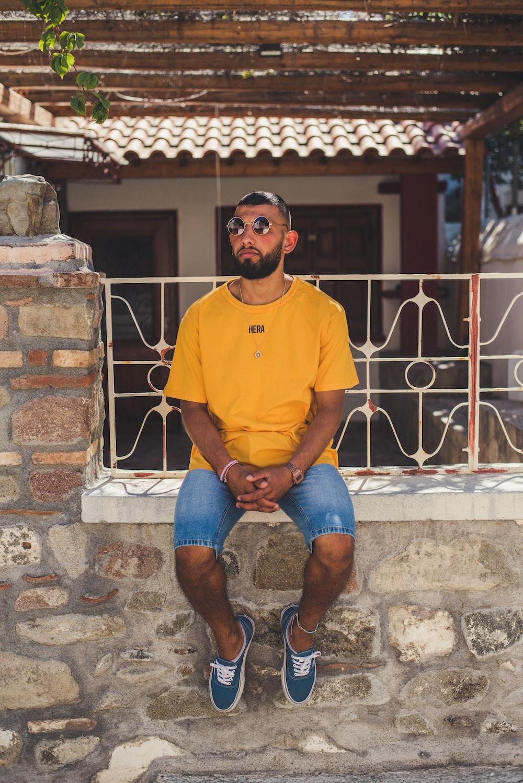 man sitting on concrete wall