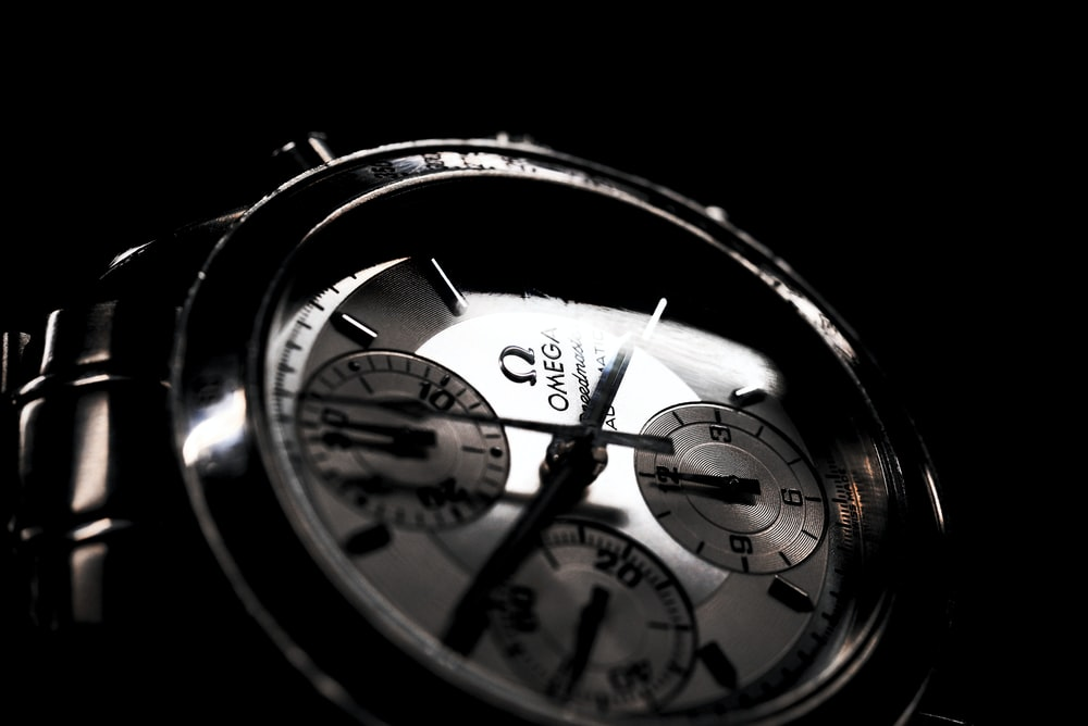 round silver-colored Omega chronograph watch