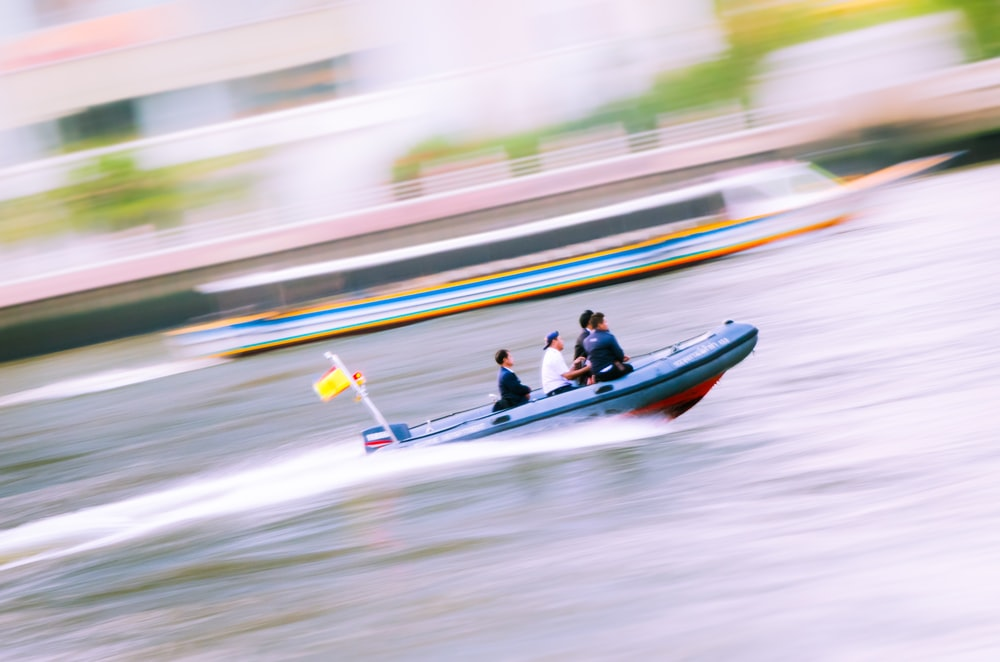 people riding ski boat during day