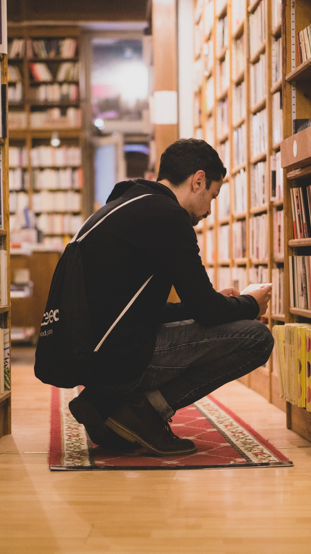 man squatting in front book shelves
