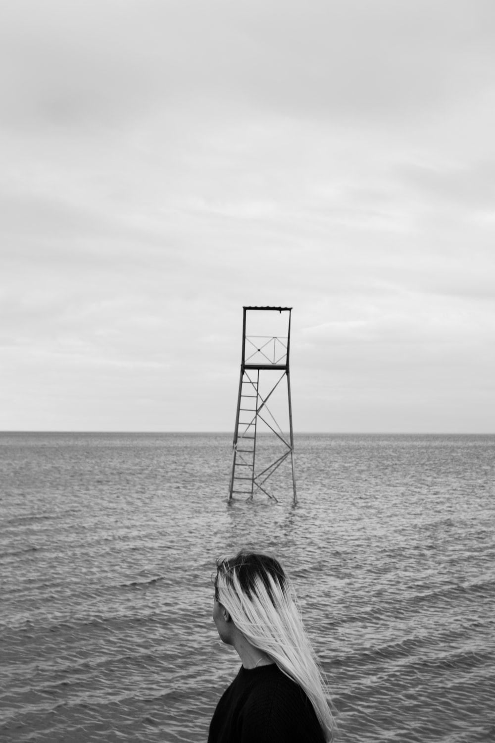 grayscale photo of woman standing beside water