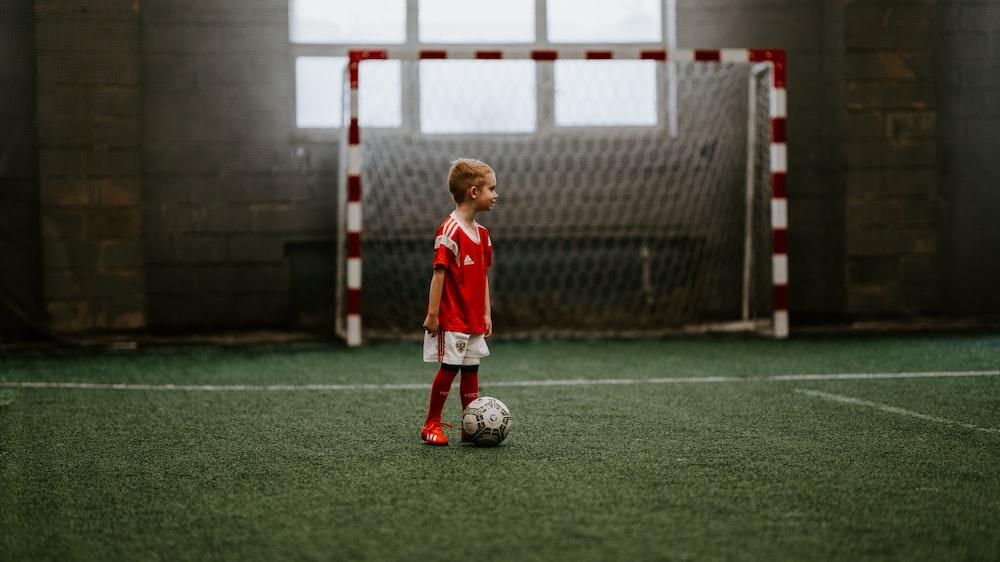 boy standing beside soccer ball near soccer net