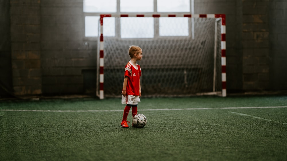 boy standing beside soccer ball near soccer net