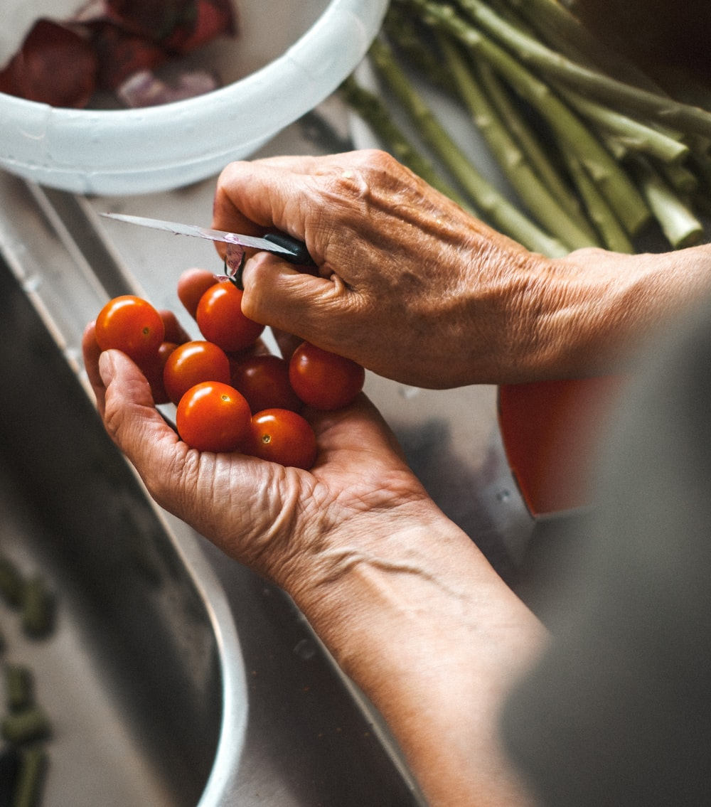 person holding knife and tomatoes