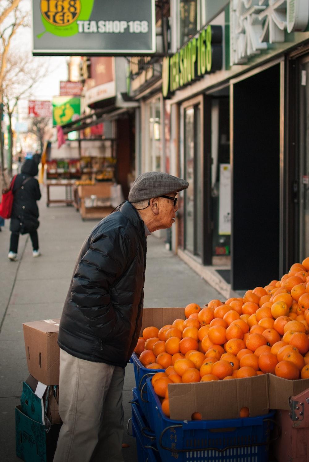 man standing beside orange fruits display