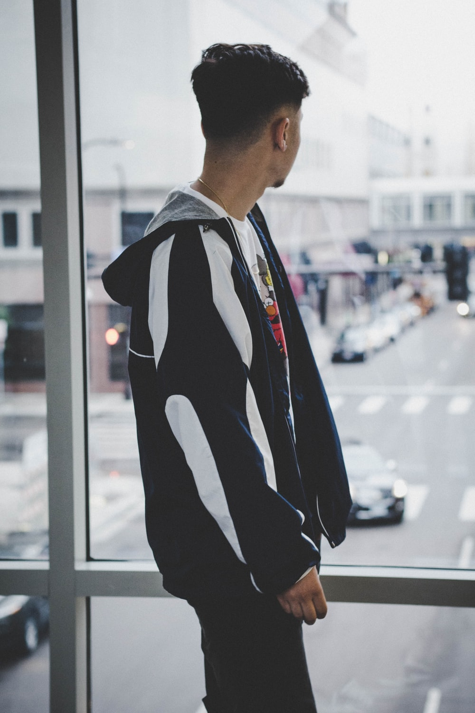 man standing beside glass window