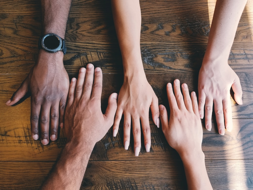 five human hands on brown surface