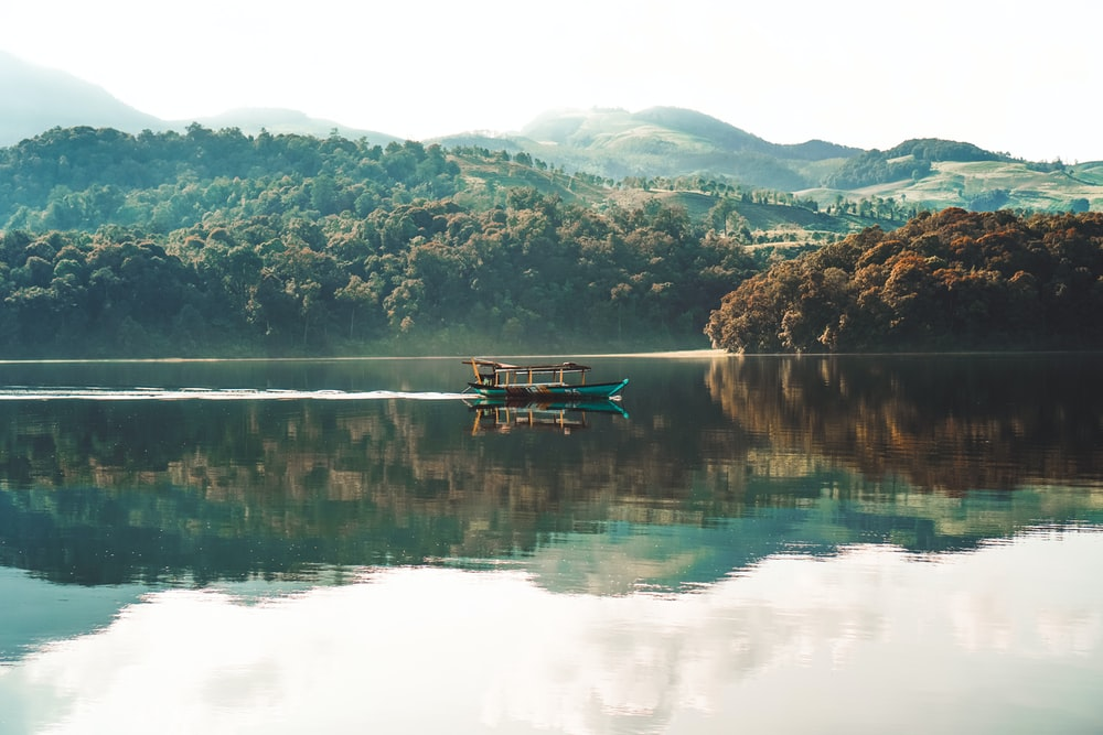 boat on calm body of water at daytime
