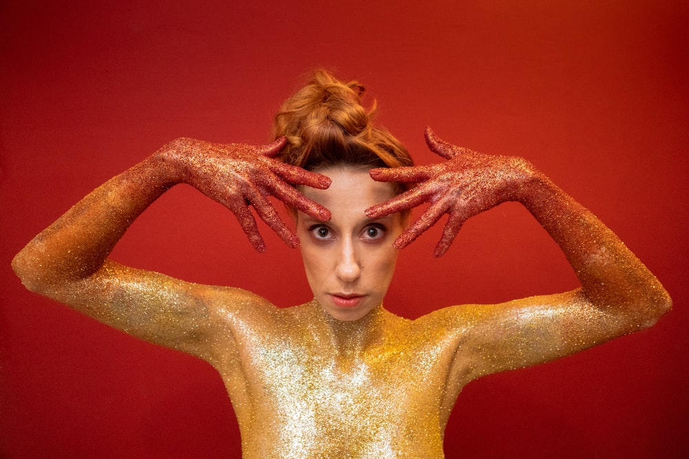 woman with gold and red dust in her body