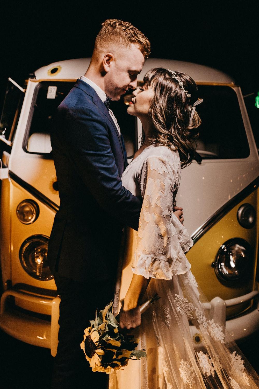 bride and groom near vehicle