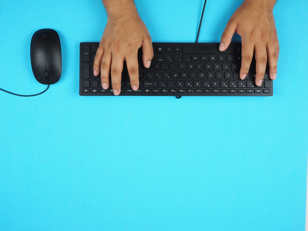 person holding black corded computer keyboard
