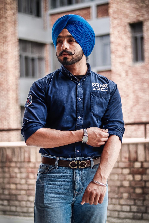 man wearing blue denim dress shirt and blue turban standing