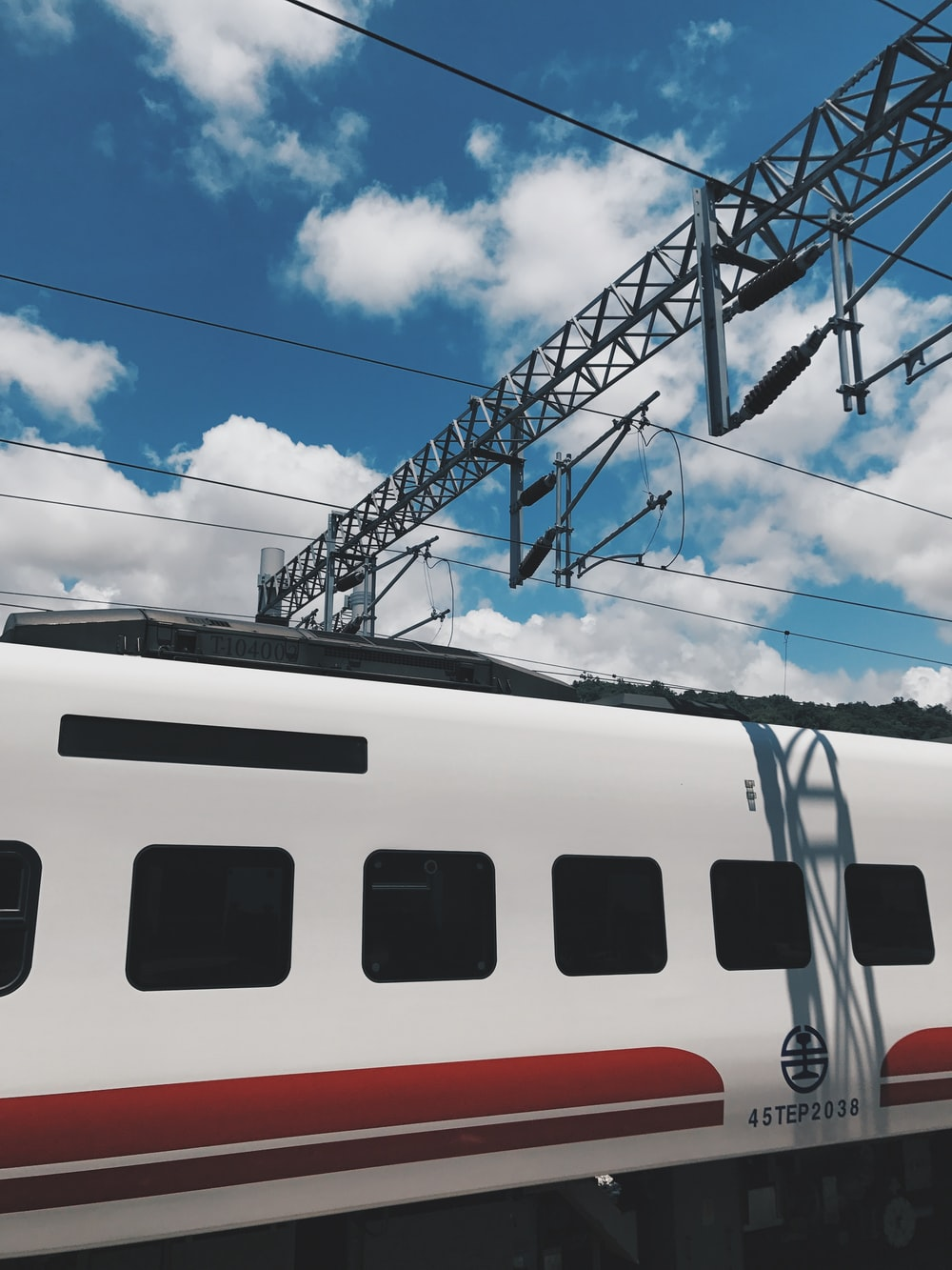 white and red train under blue sky
