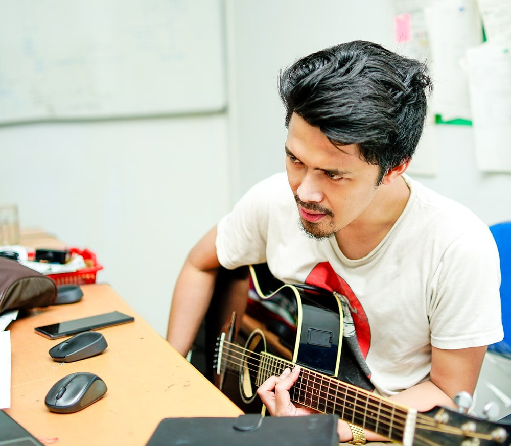 man playing guitar photography