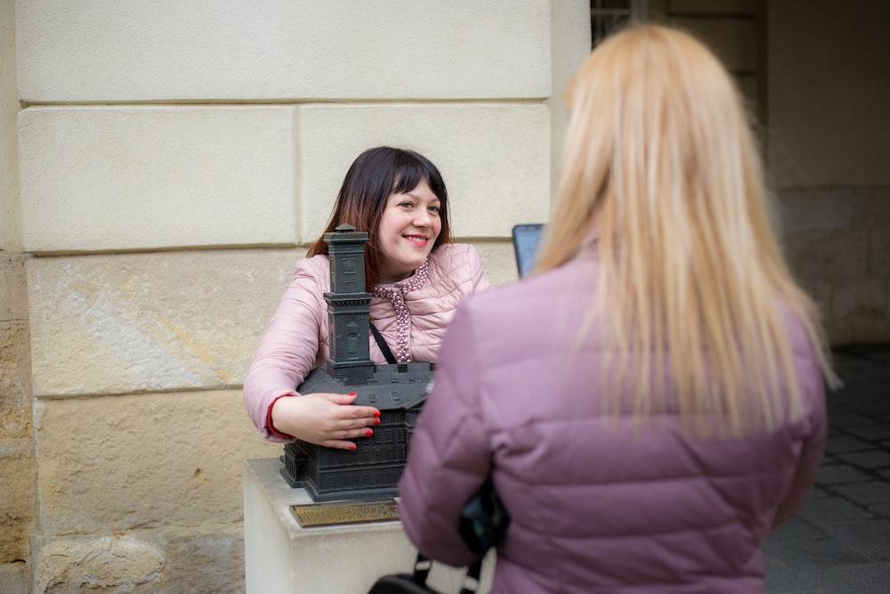 smiling woman holding black building miniature