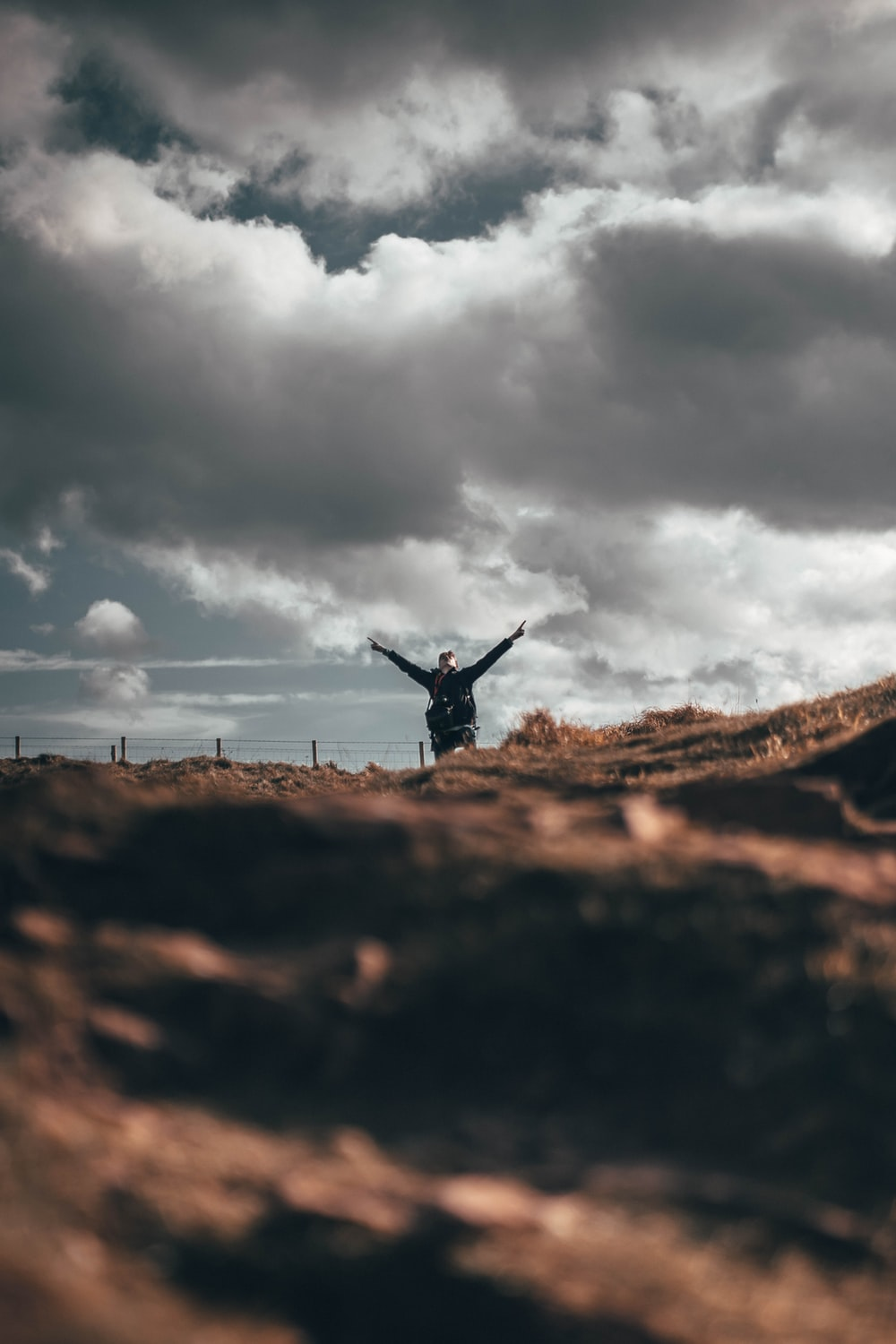 man on top of hill opening his arms wide open during cloudy day