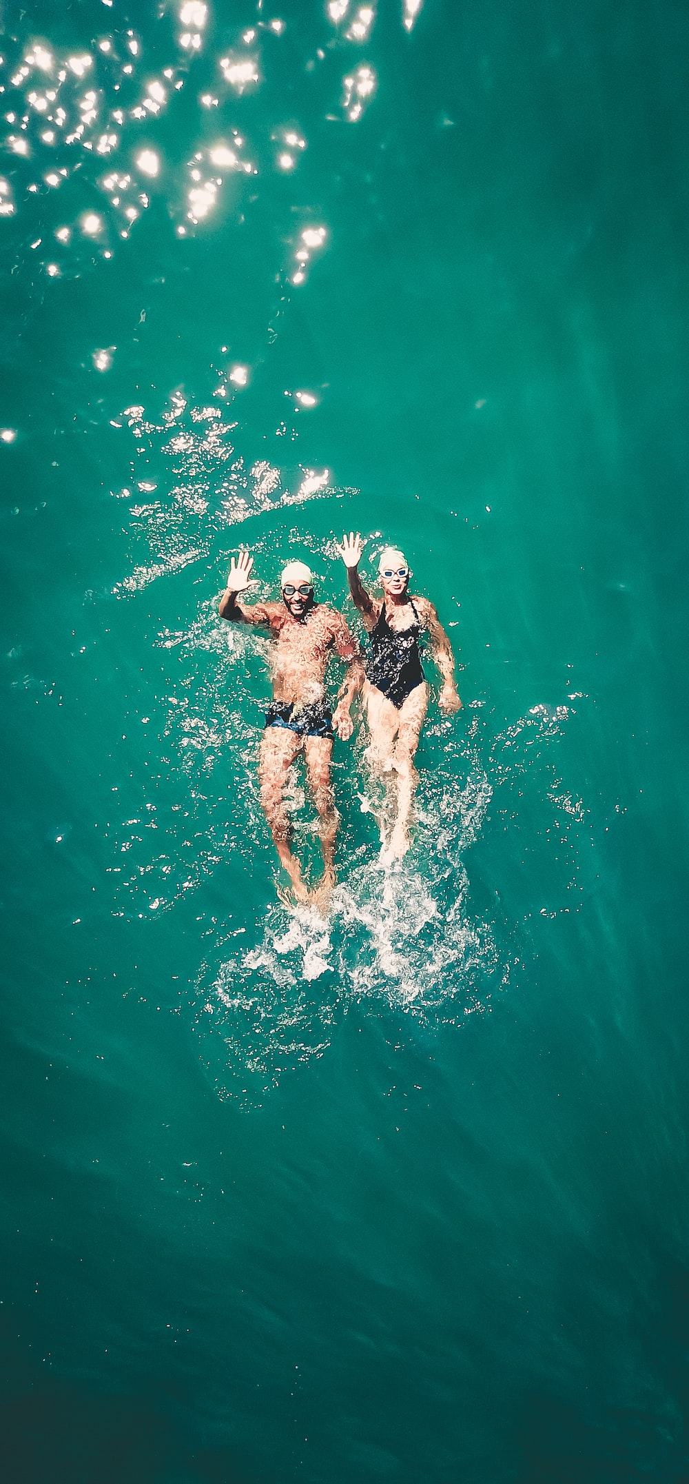 couple swimming on body of water during daytime