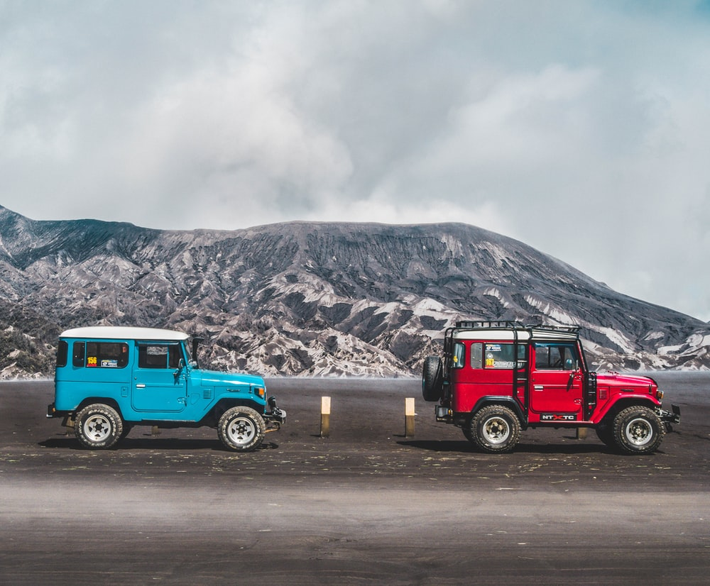 two blue and red SUV's near mountain