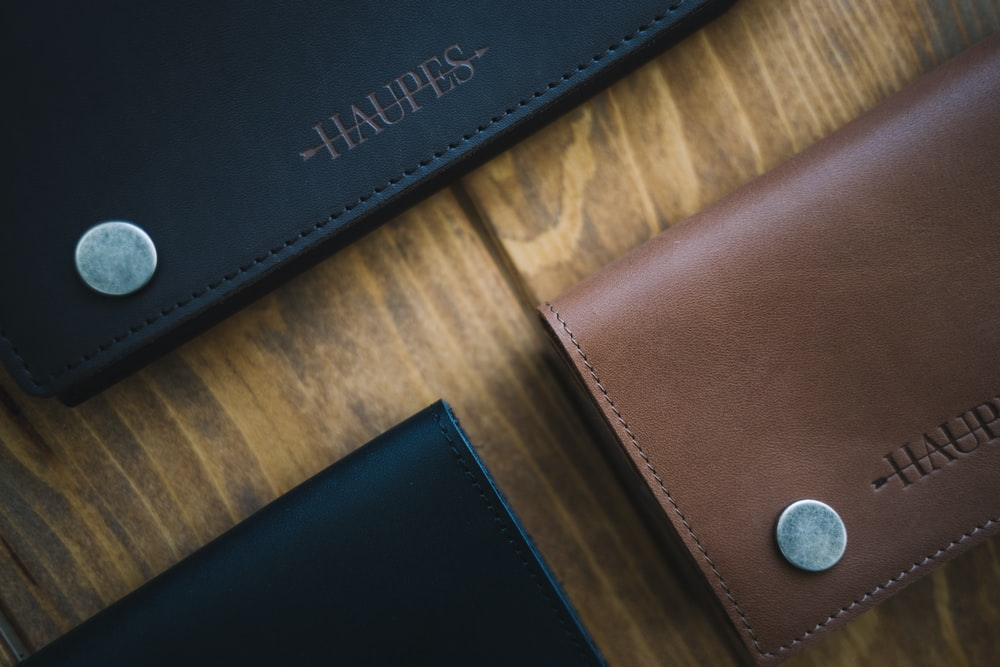 three brown and black Haupes leather wallets