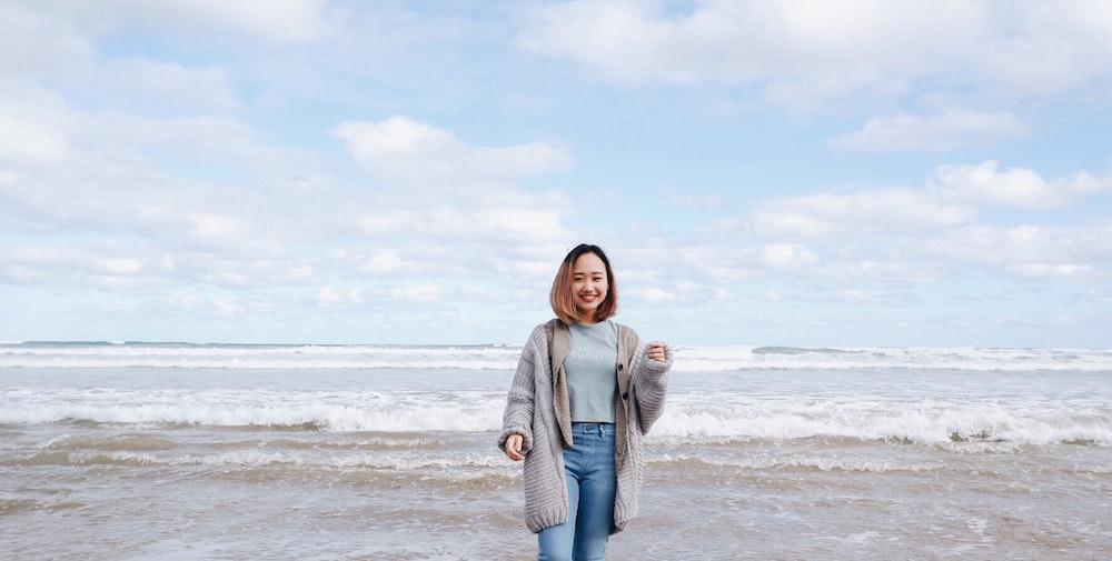 smiling woman beside sea during daytime