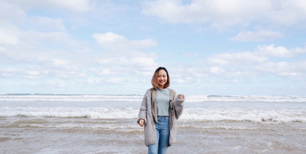 smiling woman beside sea during daytime