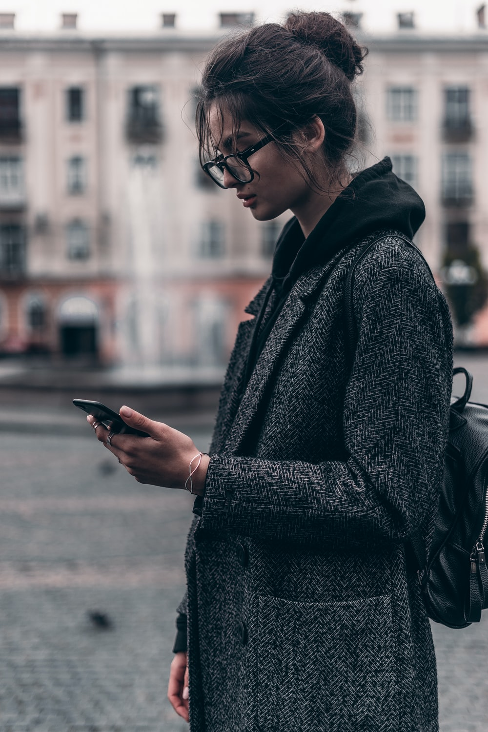 woman standing while using smartphone during daytime