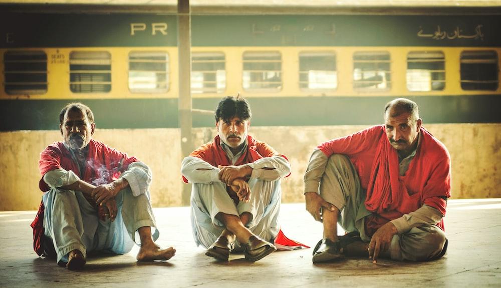 three men sitting on floor